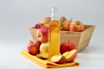 Cider vinegar bottle and red apples in a wooden basket.